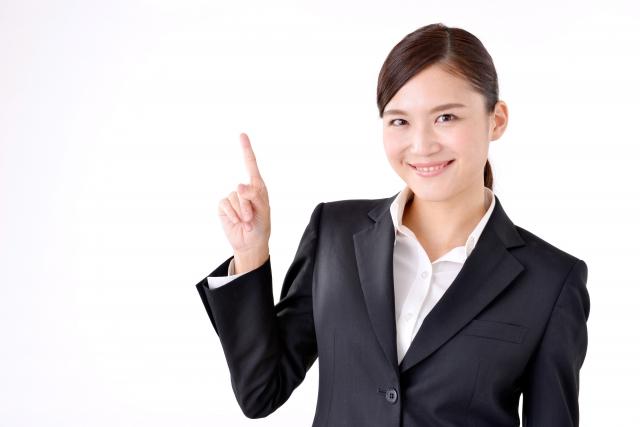 スーツ姿の女性が人差し指を立てて微笑んでいる画像