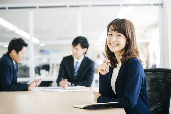 スーツの女性が笑顔でこちらをみている画像
