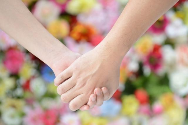 手を繋ぐ男女の写真