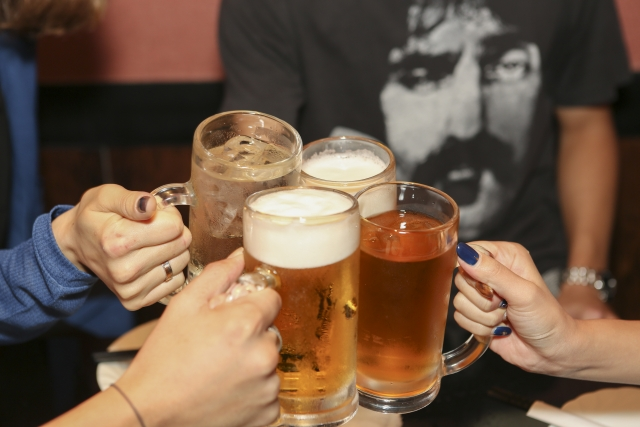 ビールジョッキを持ち乾杯している男女