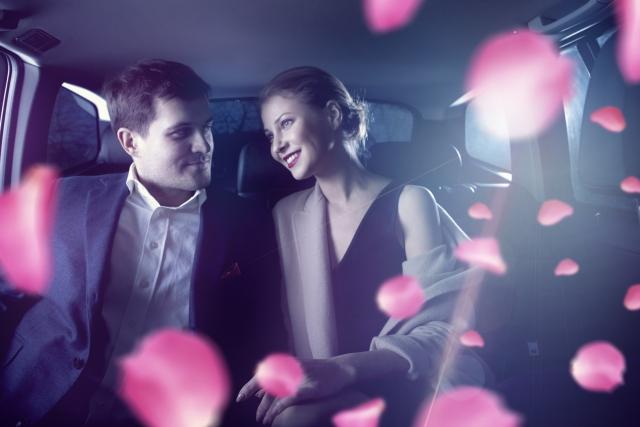 車内で男女が微笑み合っている画像