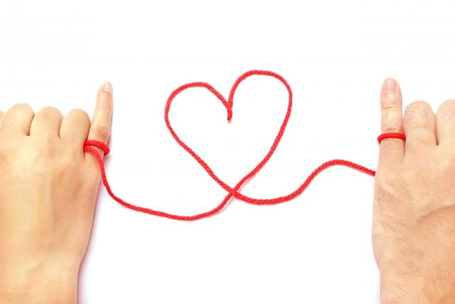 男女の小指同士を赤い糸が結んでいる画像