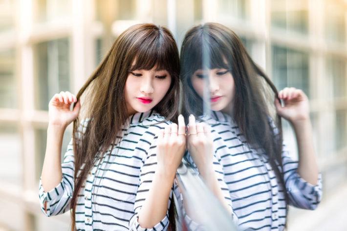 鏡にもたれかかっているアジア人の女性