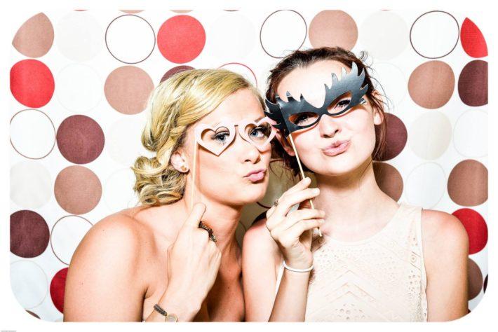 カラフルな水玉背景の前で唇を窄めて仮面を付けている外国人女性2人