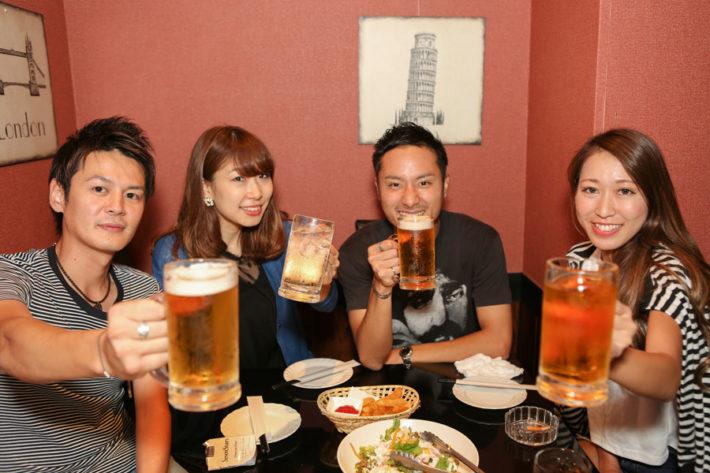 ビールジョッキを片手に乾杯している4人の男女