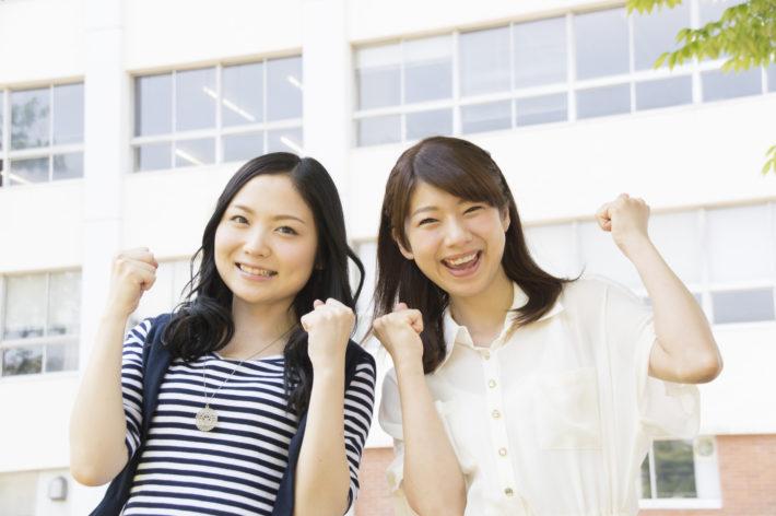 笑顔でガッツポーズをしている2人の女性