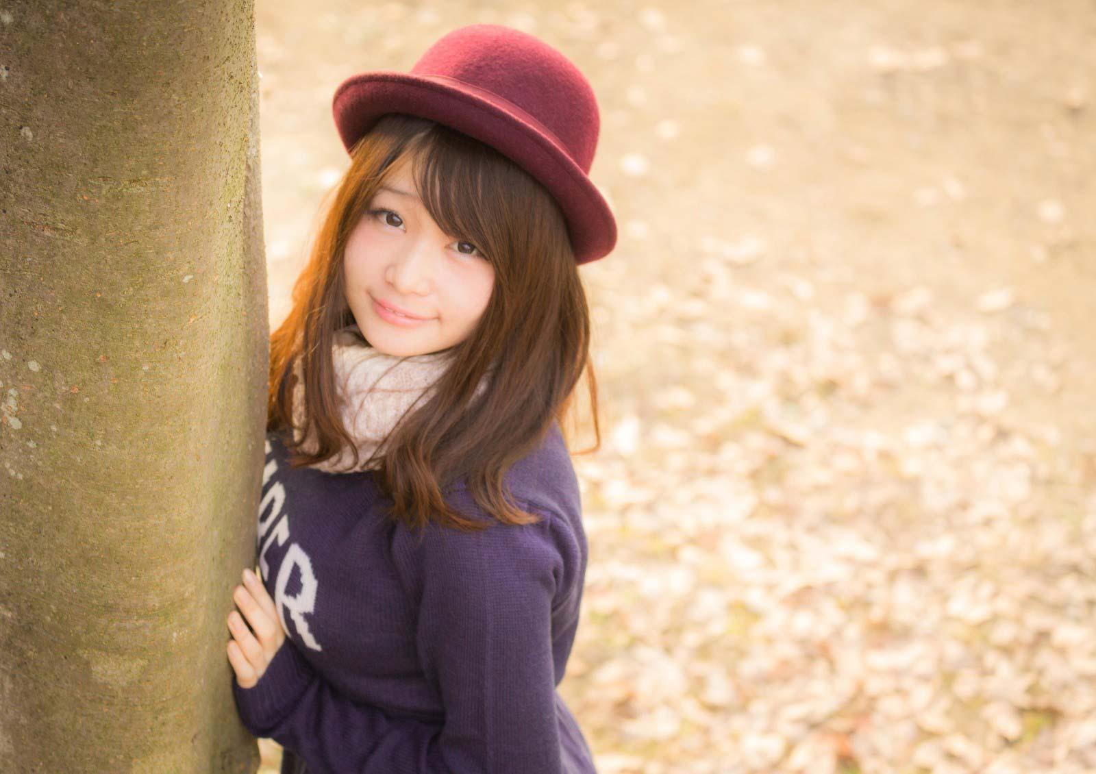 木陰から覗いている帽子を被った女性