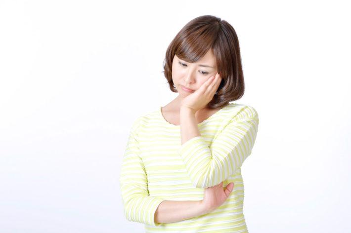 ボーダーシャツを着た女性が手を頬にあて悩んでいる画像