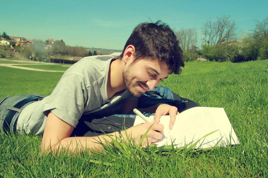 芝生にうつ伏せになり何かを書いている外国人男性