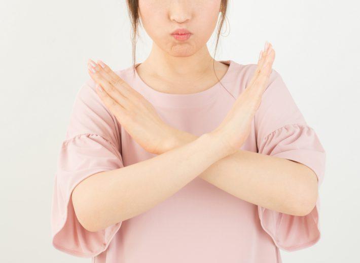 女性が唇を尖らせて腕を胸の前でクロスしている画像