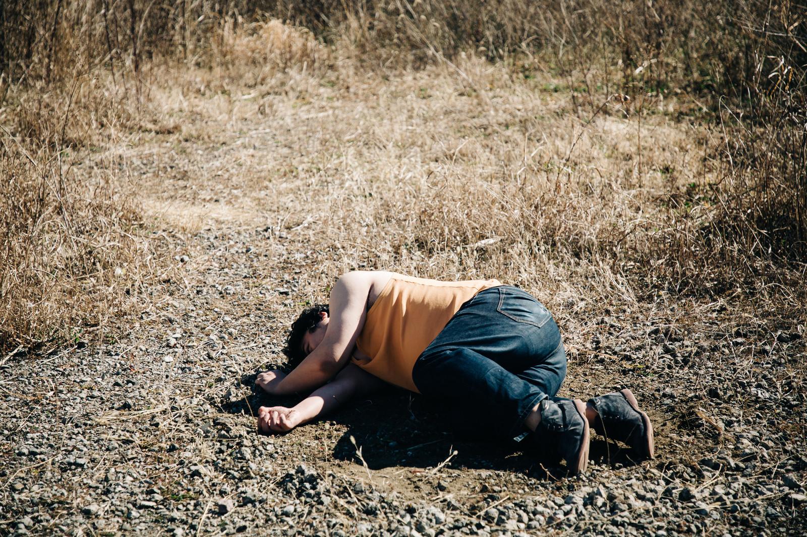 力尽きて地面に横たわる太った男性
