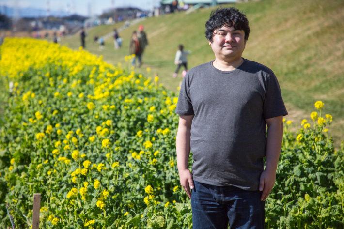 花畑をバックに立ち、微笑んでいる太った男性
