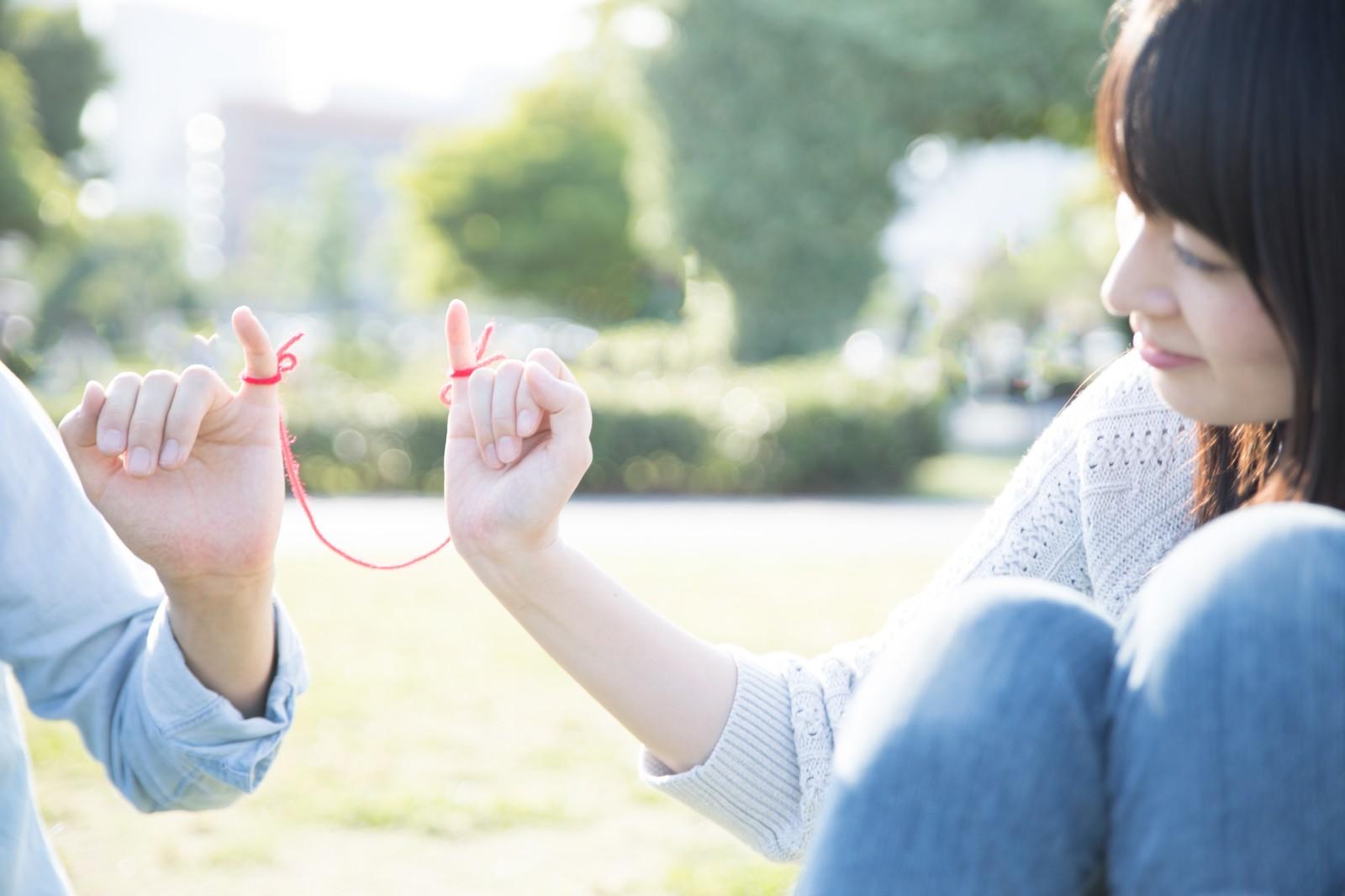 小指を赤い糸で繋ぎあった男女