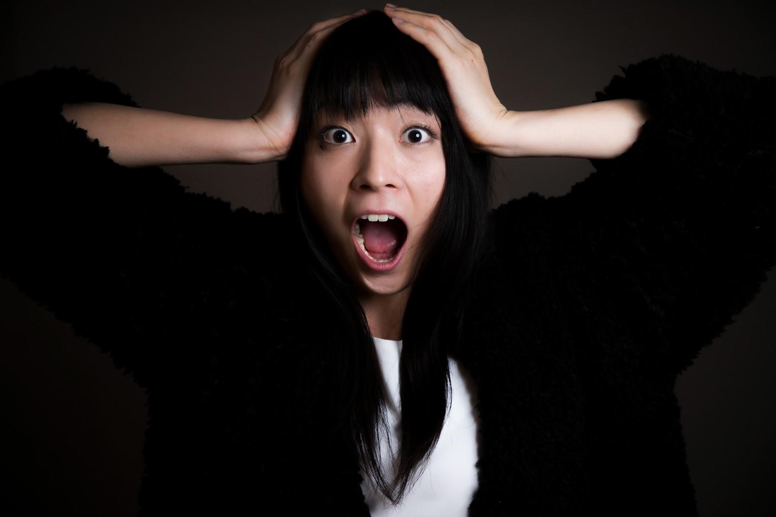 頭を抱えて叫んでいる女性