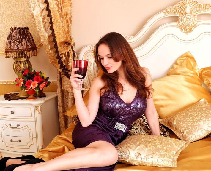ベッドの上でワインを飲んでいる女性