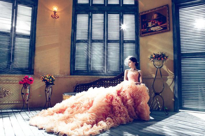ベンチに座っているピンク色のウェディングドレスを着た女性