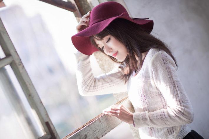 帽子を被り目を閉じている女性