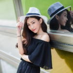 帽子を被り窓ガラスにもたれている女性