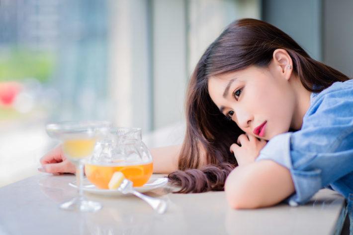 カフェのテーブルに顔を伏せて窓の外を眺める女性