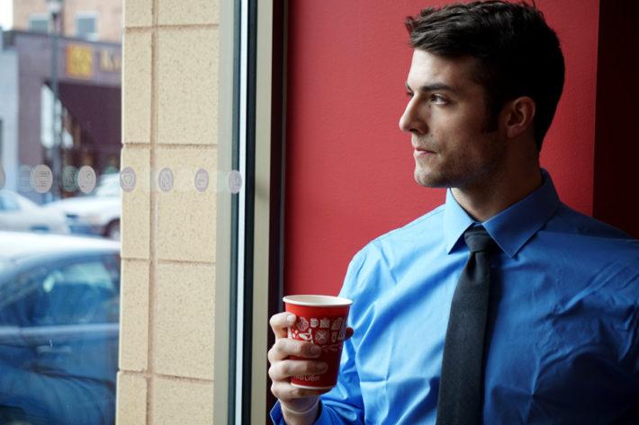コーヒーを飲むスーツ姿の男性