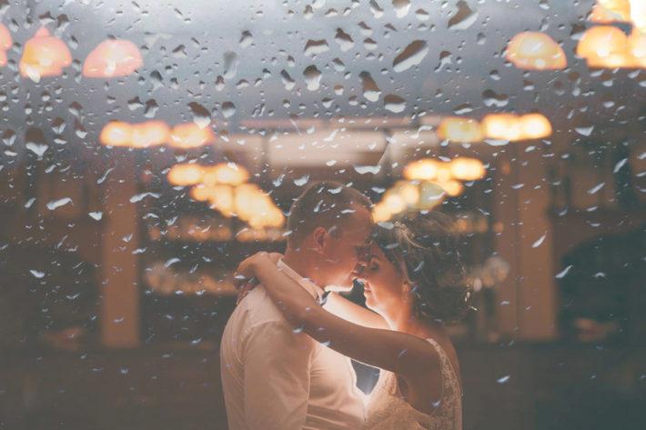 窓ガラスの前で抱きしめ合う男女