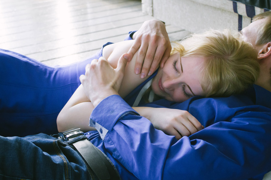 横になり抱きしめ合う外国人の男女