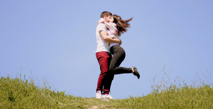 男性の胸に飛び込んでキスをしている女性