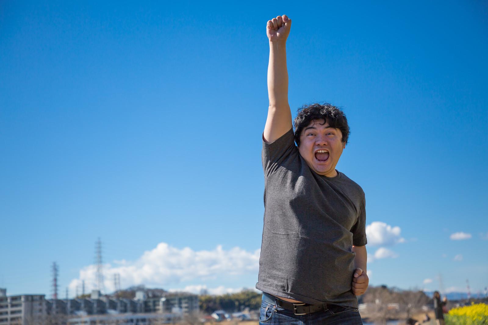 空に拳を掲げシャウトしている太った男性