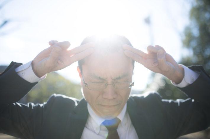 太陽を背に頭に指を当て太陽拳のポーズをとる男性