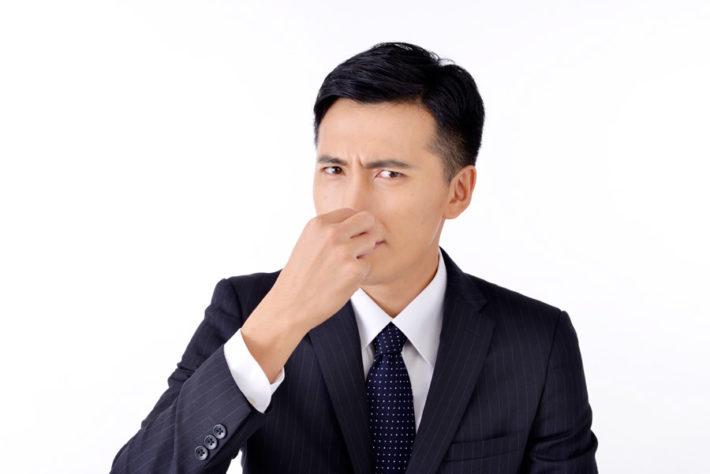 鼻をつまんでいるサラリーマン男性