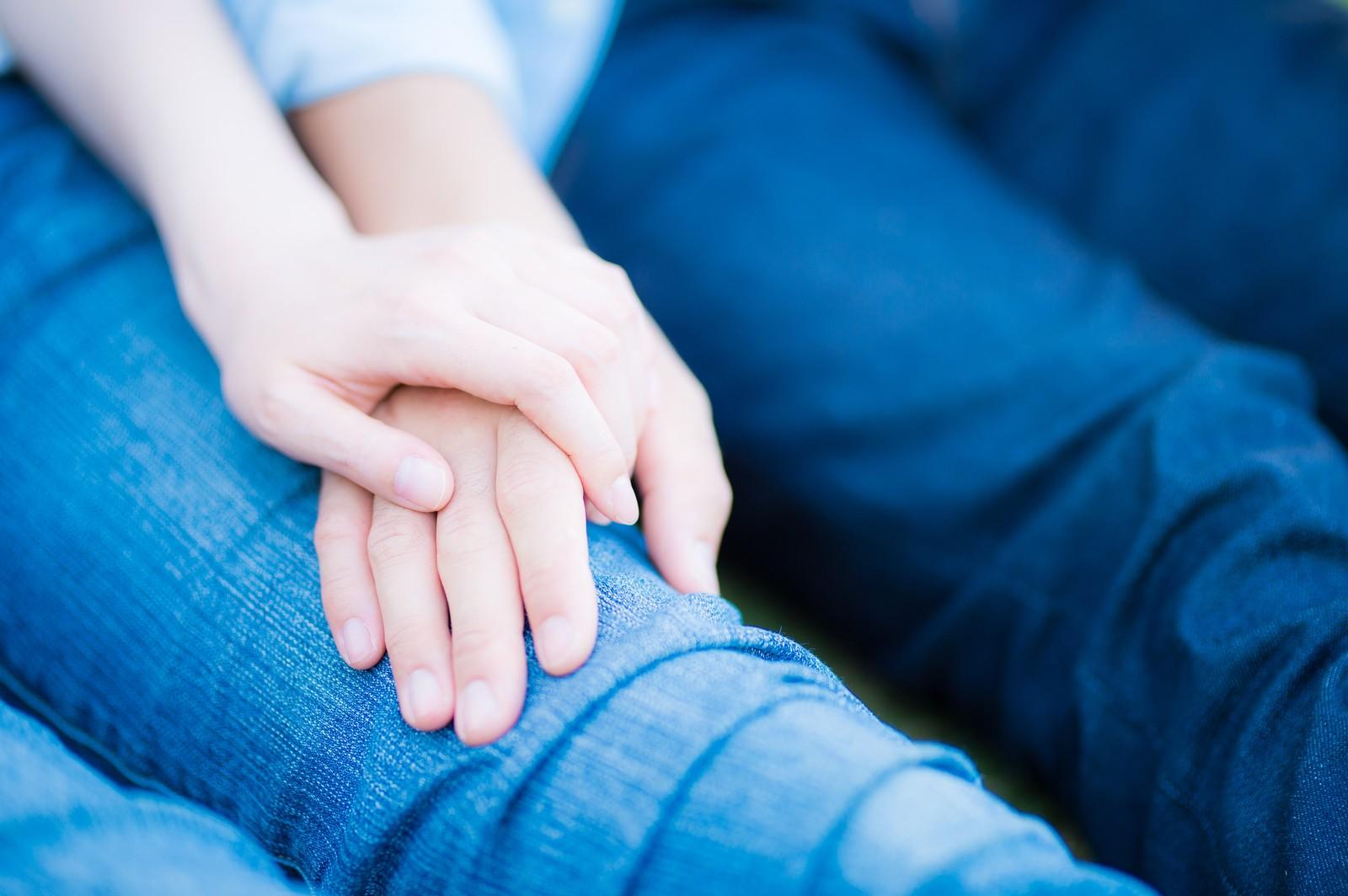 膝の上で手を重ね合っている男女