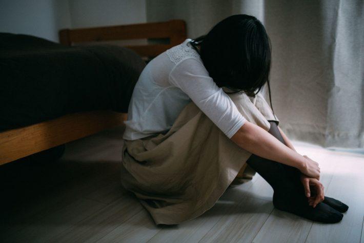 膝を抱えている女性