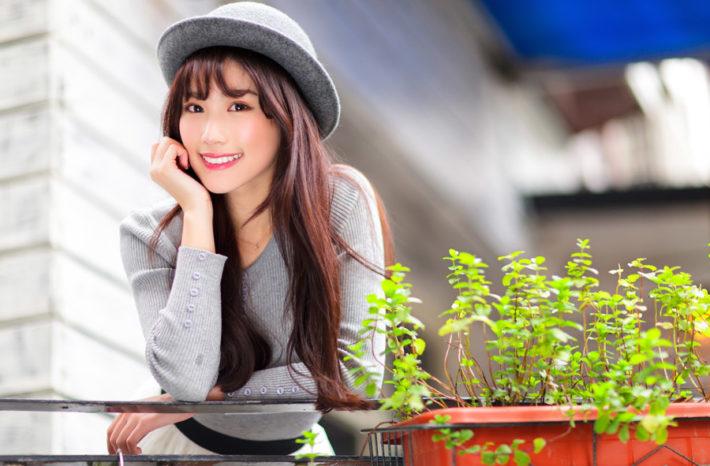 頬杖をついて微笑んでいる帽子をかぶった女性