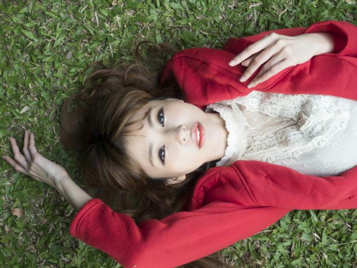 赤いカーディガンを着た女性が芝生に仰向け寝ている画像