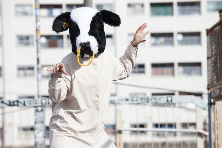 牛の被り物を被りポーズをとる女性