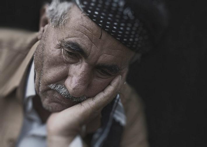頬に手をあて俯く、悲しげな表情の男性