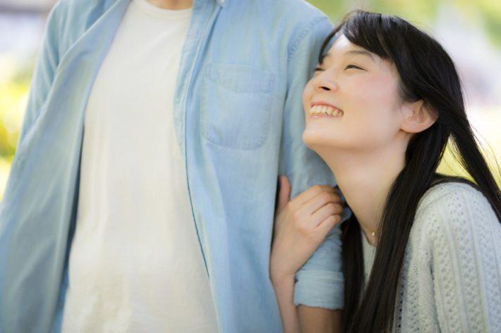 彼氏の腕を抱きしめて微笑んでいる女性