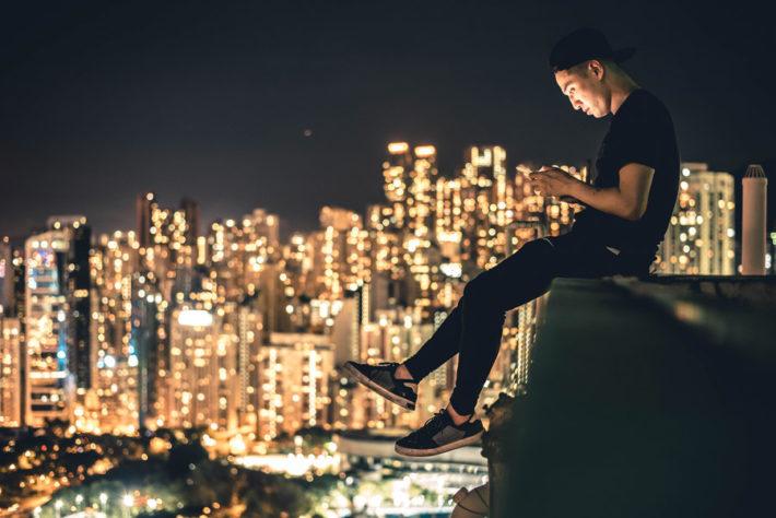 高層ビルの屋上に座ってスマホをいじっている男性