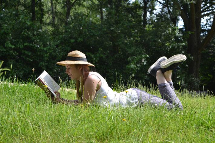 草むらに寝転び本を読む女性