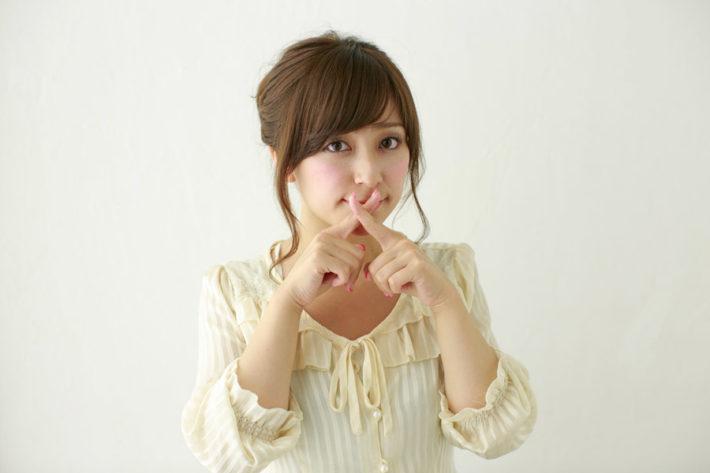 口の前でバツ印を指で作っている女性