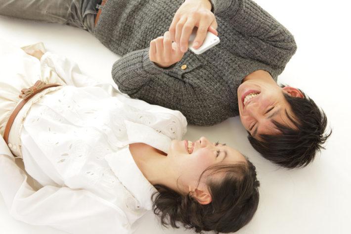 寝転んで笑い合う男女