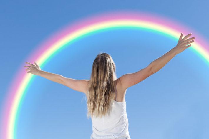 空にかかった虹を両手を広げ見つめている女性