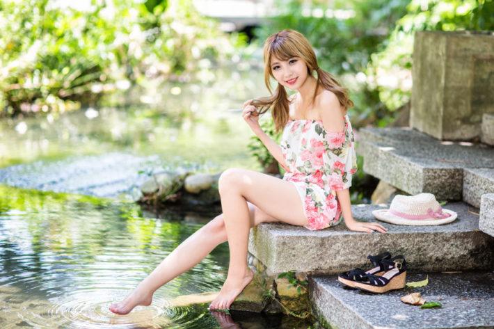 小川のほとりにある石に腰掛けて微笑んでいる女性