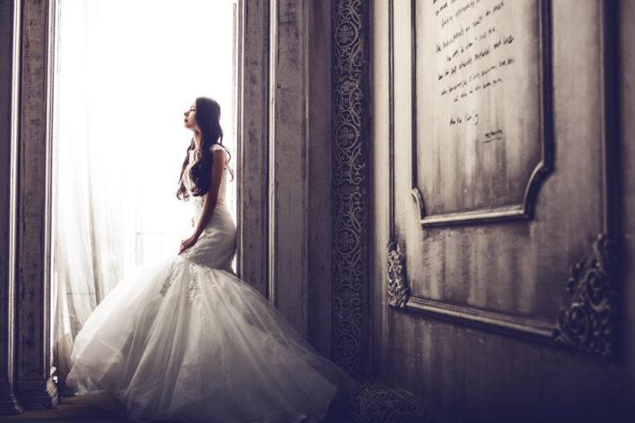 石碑の前でウェディングドレス姿の女性