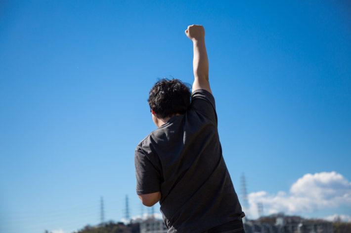 太陽に向かってガッツポーズしているオタク男性の背中