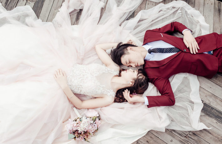 礼服とウェディングドレスを身にまとい、床に横たわっている男女