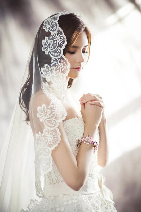 ウェディングドレスを着て祈っている女性