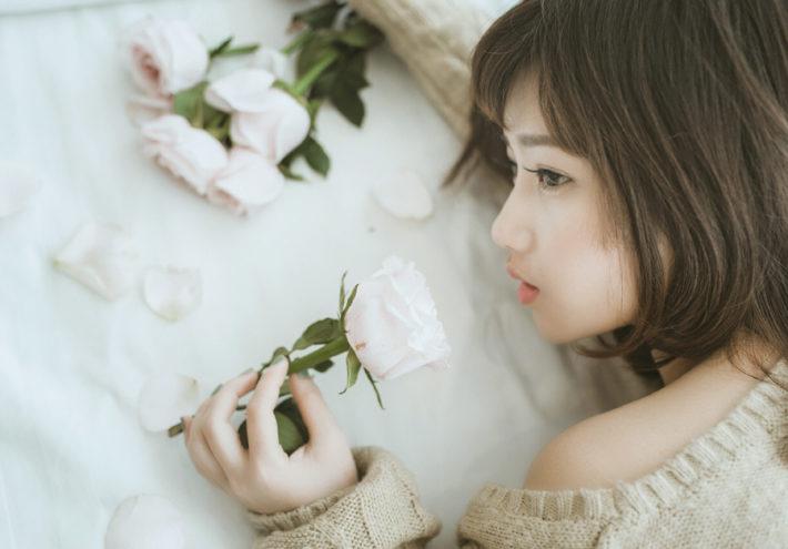 バラの花を持ちうつ伏せになっている女性