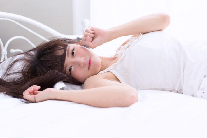 ベッドに横になりこちらを見ている女性
