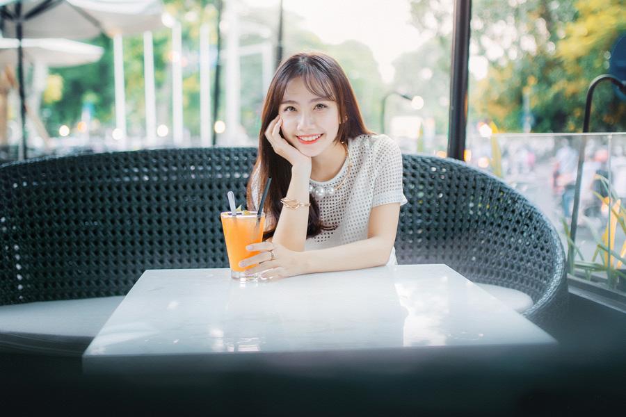 カフェでジュースを飲んで微笑んでいる女性